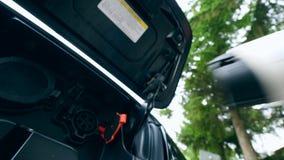Mannen tar bort laddande kabel från en elbilhålighet Uppladdning av elbilen lager videofilmer