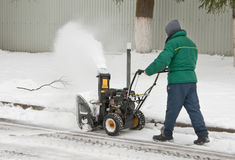 Mannen tar bort snö, genom att använda en snö som kastar maskinen Royaltyfri Foto
