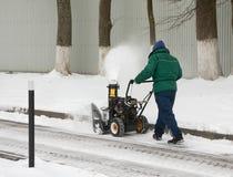 Mannen tar bort snö, genom att använda en snö som kastar maskinen Fotografering för Bildbyråer