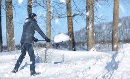 Mannen tar bort snö med skyffeln från vägen i snöig vinter arkivbild