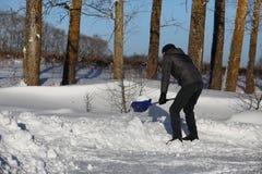 Mannen tar bort snö med skyffeln från vägen i vinter arkivfoton