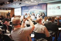 Mannen tar en bild av presentationen på konferenskorridoren genom att använda smartphonen royaltyfri bild