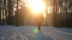 Mannen tar en gå till och med härlig snöig skog stock video
