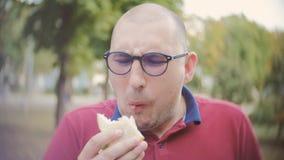 Mannen tar en tugga av hans smörgås och förskräcktes för att finna att den stillösa smörgåsen långsam rörelse stock video