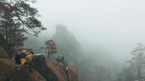 Mannen tar en video på hans smartphonesammanträde på överkanten av vagga någonstans i bergen som täckas med snö lager videofilmer