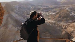 Mannen tar foto av det fantastiska ökenlandskapet Europeisk manlig turist med kameran på den massiva bergsikten Israel 4K lager videofilmer