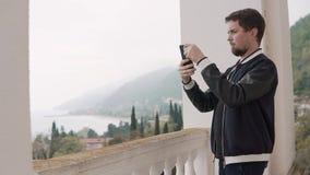 Mannen tar foto av landskapet på telefonen, som han ser igenom fönstret arkivfilmer