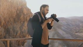 Mannen tar foto av massivt berglandskap Caucasian man med kamerafotografier och blickar på hans kamera Israel 4K lager videofilmer