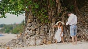 Mannen tar fotoet av den härliga kvinnan i hatt, och vitklänningen på en kamera under trädet med rotar utomhus Lyckligt le royaltyfria foton