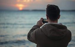 Mannen tar fotografisolnedgång över havet Royaltyfri Foto