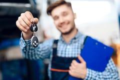Mannen tar hans bil från den auto servicen Mekanikern överför biltangenterna till kunden royaltyfri foto