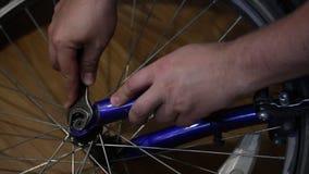 Mannen tar hjulet av cykeln Skruva av muttern med en skiftnyckel stock video