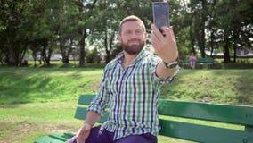 Mannen tar selfie på bänk parkerar in steadicam stock video