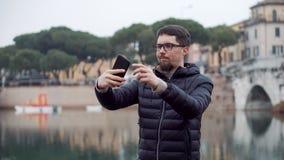 Mannen tar selfies vid mobiltelefonen med gränsmärken stock video