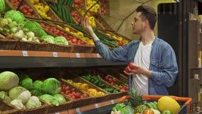Mannen tar tomater och gurkan från kuggen på supermarket royaltyfria bilder