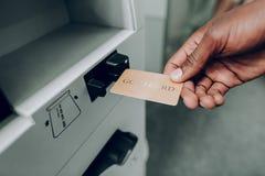 Mannen tar ut banken det guld- kortet in i en ATM-maskin fotografering för bildbyråer
