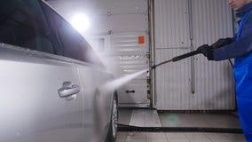 Mannen tvättar bilen med högtryckvatten arkivfilmer