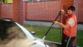 Mannen tvättar bilen, tvättar sig genom att använda högtryckvattenstrålen färgstänk fördelade till sidor lager videofilmer