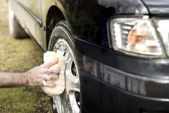 Mannen tvättar en bilsvamp med ett bilschampo för aluminum legering Royaltyfri Foto
