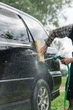mannen tvättar hans bil på bakgrund av gräsplanträdgården royaltyfria foton