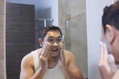 Mannen tvättar hans framsida i badrum royaltyfri foto