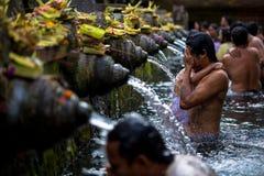 Mannen tvättar hans framsida på Tirtha Empul arkivbild