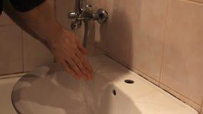 Mannen tvättar hans händer under vattenkranen lager videofilmer
