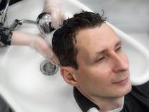Mannen tvättar hans hår efter en frisyr royaltyfri foto