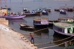 Mannen tvättar kläder på bankerna av floden Ganges med gamla fartyg omkring Arkivbild