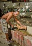 Mannen tvättar hans hund på en lokal parkerar i havannacigarr Royaltyfri Bild