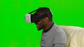 Mannen tycker om att hålla ögonen på video i VR-maskering grön skärm arkivfilmer