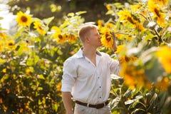 Mannen tycker om doften av solrosen royaltyfri fotografi