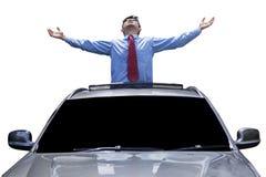 Mannen tycker om frihet på soltaket av bilen Arkivfoto