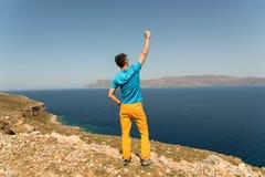 Mannen tycker om hans semester i Grekland nära havet Arkivfoto