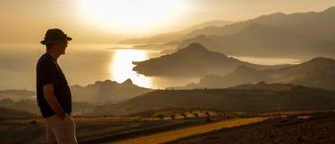 Mannen tycker om sikt av havet och montains i solnedgångtid Arkivfoto