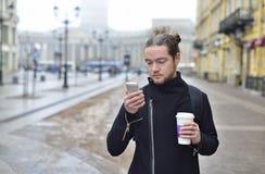Mannen tycker om telefonen och innehavet per koppen kaffe Arkivfoto