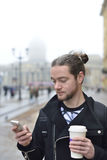 Mannen tycker om telefonen och innehavet per koppen kaffe Royaltyfri Bild