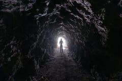 Mannen undersöker en grotta Arkivfoto