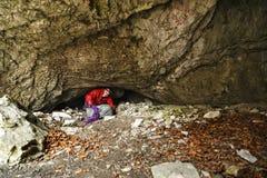 Mannen undersöker en grotta Fotografering för Bildbyråer
