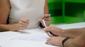 Mannen undertecknar ett dokument och mottar kreditkorten stock video