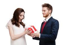 Mannen undrar hans flickvän med presenten Royaltyfri Foto