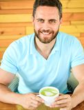 Mannen uppsökte grabben dricker cappuccino på trätabellkafét Koffein kan få idérika fruktsafter som flödar, då du klibbade i brun royaltyfria foton