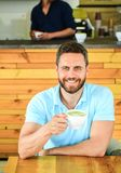 Mannen uppsökte grabben dricker cappuccino på trätabellkafét Tycker om den lyckliga framsidan för kafébesökaren kaffekoffeindrink royaltyfri bild