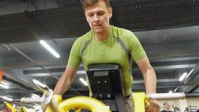 Mannen utarbetar på idrottshallen på simulatorer sport Sund livsstil stock video