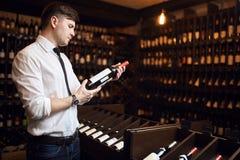 Mannen utbildas i vinavsmakning som parar vin med foods, att inhandla för vin royaltyfri fotografi