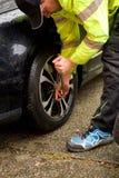 Mannen utbyter de säsongsbetonade hjulen Fotografering för Bildbyråer