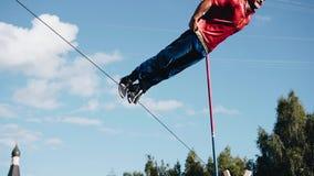 Mannen utför en rotation runt om dess axel som binds till repet Hans ben binds till repet 360 grad rotation arkivfilmer