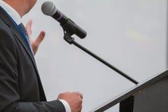 Mannen utför på konferens - talar i mikrofonen för åhörare Royaltyfri Foto