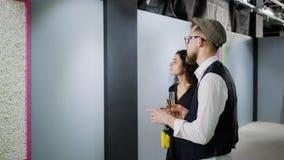 Mannen utför utfärd i konstgallerit för nätt brunettkvinna arkivfilmer