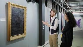 Mannen uttrycker hans åsikt om bild i konstgallerit, kvinna lyssnar lager videofilmer